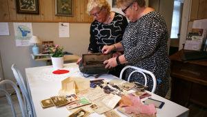 Aira Hellström och Marja-Leena Suvitie, två damer med glasögon och svartvita klänningar, har på köksbordet brett ut innehållet från en gammal handväska. På bordet finns fotografier, ransoneringskuponger och identitetskort.