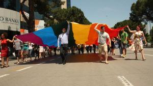 Deltagare i Pridefestivalen i Tirana håller upp prideflagga