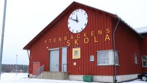 En röd trähusfasad med texten Stenbackens skola uppristad på väggen med stora bokstäver. Ovanför texten en stor klocka.