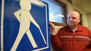 människa invid trafikmärke som föreställer en person med käpp