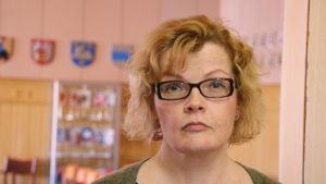 En kvinna med axellångt ljus hår och glasögon står i en dörröppning.