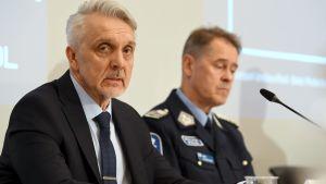 En man i kostym och en man i polisuniform sitter vid ett bord.