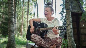 Nainen istuu penkillä risti-istunnassa, soittaa kitaraa ja laulaa, taustalla keväistä metsää