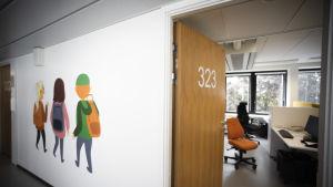 En korridor i ett familjecenter. På den högra sidan en öppen dörr till ett arbetsrum. På vänstra sidan illustrationer på barn på korridorsväggen.