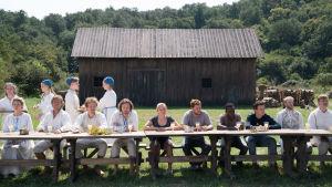 Midsommargästerna i Hårga sitter alla vid ett långbord utomhus.