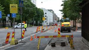 Byggarbetsplats vid Trädgårdsgatan. En person dirigerar trafiken.