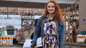En kvinna står på Karis järnvägsstation. Det är en byggarbetsplats med byggställningar, halvfärdig bro och ett tåg bakom henne