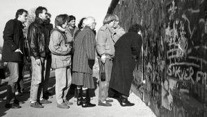 Människor tittar igenom ett hål i Berlinmuren 11.11.1989.