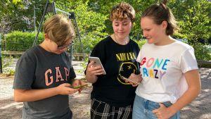 Ungdomar som kollar på sina telefoner.