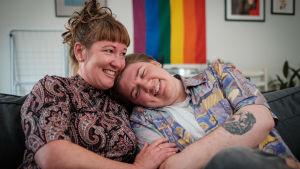 en mamma kramar om sin son som är trans, de ler och sitter på soffan tillsammans.