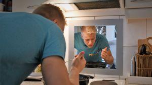 Emil Soravuo står vid spisen och kockar.