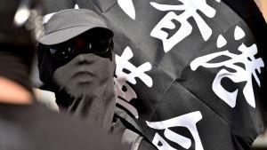 På söndagen hölls stöddemonstrationer för Hongkong i flera städer runt om i världen. Här en maskerad demonstrant i Sydney, Australien.
