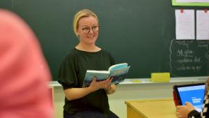 Lärare sitter med bok i klassrum.