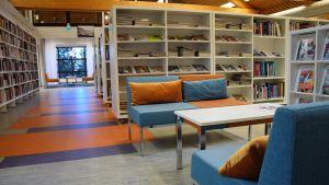 Korridor i ett bibliotek med soffor och bord.
