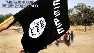 Svart flagga med arabisk text vajar i IS-propagandafilm.