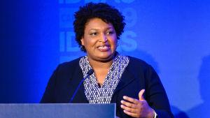 Stacey Abrams står bakom ett podium och talar i en mikrofon.