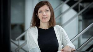 Eleanor Coffey, en brunhårig kvinna med vit kofta och svart t-skjorta står i en trappa