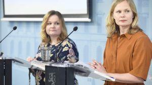 Krista Kiuru och Hanna Kosonen står vid talarpodium framför en blå vägg. De tittar åt sidan.
