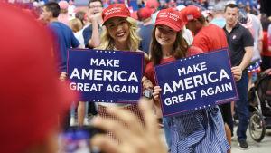 Kaksi hymyilevää tyttöä pitelee käsissään kylttejä, joissa lukee Make America great again.