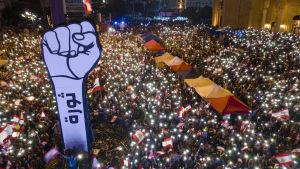 Demonstranter håller upp mobiler med tända ficklampor.