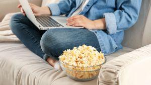 En person sitter på en soffa med dator i famnen. Bredvid henne syns en skål med popcorn.