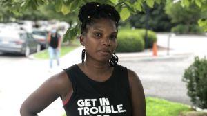 """En kvinna står på gatan i Washington med en t-shirt där det står """"get in trouble. necessary trouble."""""""