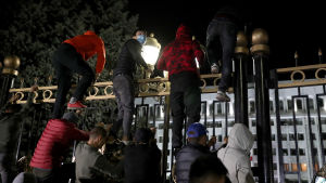 Demonstranter klättrar över stängslet till parlamentshuset i Kirgiztans huvudstad Bisjkek.