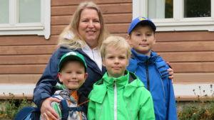 En kvinna och tre barn, pojkar, utanför en skola. Bromarv. Höst