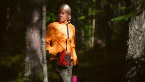kaisa i skogen med bärplockare och hink i handen