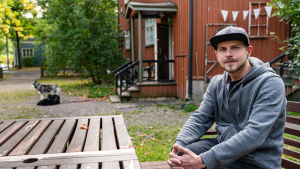 En man sitter utanför ett rött trähus. Han ser mot kameran och ler, men ser bestämd ut. Två hundar ligger på marken framför huset.