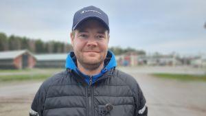 Ung man med keps och blå huvtröja och jacka står framför en minkfarm och ser in i kameran.