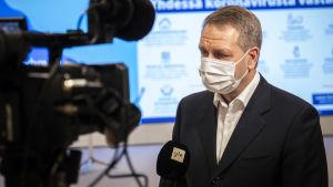 Jan Vapaavuori intervjuas av Yle. Han är klädd i kostym och munskydd.