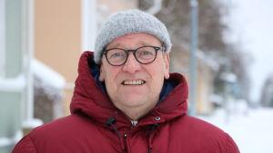 En man glasögon, grå mössa på huvudet och en röd dunjacka med huva, står på en vinterklädd gata.