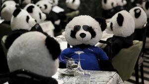 Leksakspandor sitter placerade runt bord med dukar och glas. Pandan i förgrunden har blå tröja, solglasögon.