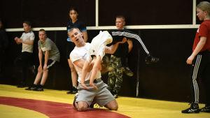 Jerry Kvarnström hjälper en junior med en rörelse under brottningsträningar i Åbo i januari 2021.