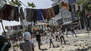 Demonstranter hänger upp saronger över en gata i Rangoon, för att avskräcka säkerhetsstyrkorna. I Myanmar anses det medföra otur för män om de passerar under kvinnokläder som hänger på tork.