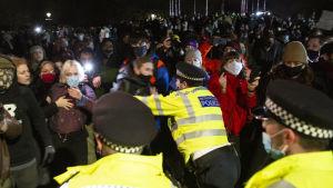 En polis ser ut att knuffa undan en demonstrant.