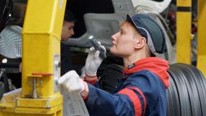 Autotyöläinen Tanja Leino tehtaalla taskulampun kanssa.