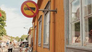 Keltaisen puutalon seinässä liikennemerkki, kadulla pöytiä, tuoleja ja ihmisiä.