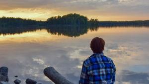 Ihminen istuu auringonlaskussa järven rannalla
