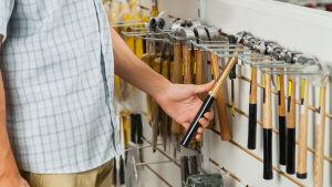 En person står i en järnhandel och tittar på olika hammare.