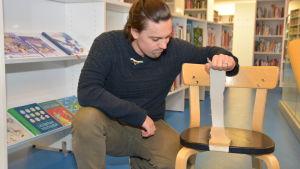 Benjamin Lundin visar en trasig stol i Ingå bibliotek.