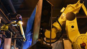 Den japanska roboten lyfter upp en komprimator till en sopbil och svetsroboten svetsar ihop den.