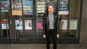 Jessica Mattila står utanför ritz dörr som är fylld av evenemangsplanscher. Hon bär en svart läderjacka.