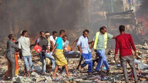 Män bär på en bår med ett av offren för bombdådet utanför hotel Safari i Mogadishu på lördagen.