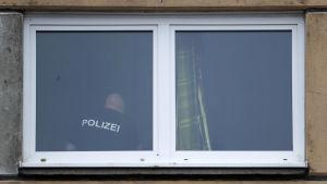 Fönster till razzialägenheten, där en polisman syns genom fönstret.