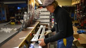 Man avlägsnar plast från ett par slalomskidor.