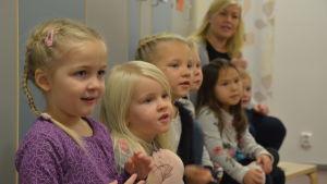 Många barn sitter på en bänk och lyssnar noga. De ser förväntansfulla ut.
