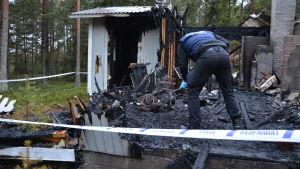 Polis gräver bland förkolnat bråte.
