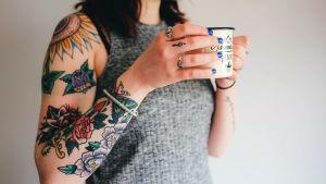 tatuoitu nainen pitää kahvikuppia kädessä